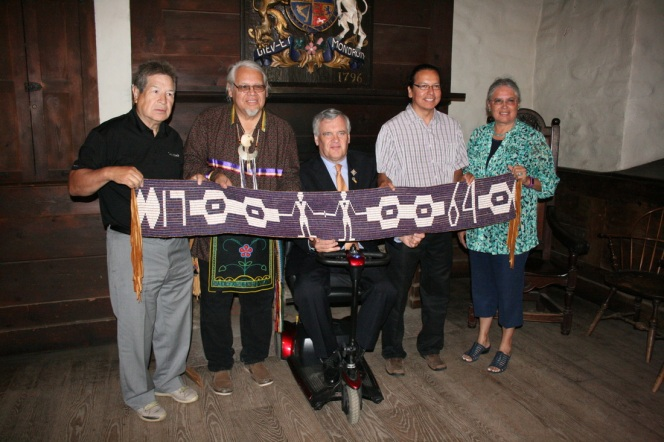 """Grand Chief Gord Peters, Professor Rick Hill, The Hon. David C. Onley, Lieutenant Governor of Ontario, Professor Alan Corbiere and Chief Ava Hill stand in the Johnson Room of Fort Niagara's """"French Castle"""" holding the Covenant Chain Wampum (1764) during the 250th commemoration feast of the Treaty of Niagara hosted by the Haudenosaunee and Anishinaabe Nations on August 1st, 2014."""